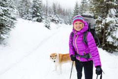 Happy woman walking in winter forest with dog Stock Image