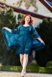 Happy woman walks in a park. Happy redheaded woman walks in a park with flowing dress Stock Photos