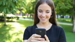Happy woman walks in a park using phone stock footage