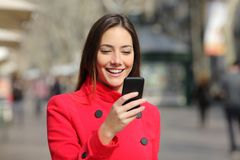 Happy woman walks using phone in winter in the street. Happy woman wearing red jacket walks using smart phone in winter in the street stock images
