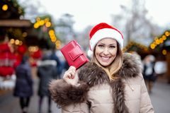 Happy woman with wallet at the christmas market stock photo