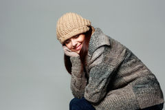 Happy woman in warm winter outfit on gray background Stock Image
