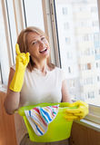 Happy woman washes window in the new apartment Royalty Free Stock Photo