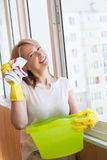 Happy woman washes window in the new apartment Royalty Free Stock Image