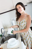 Happy woman washing dishes in home Royalty Free Stock Photography