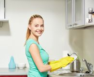 Happy woman washing dishes at home kitchen Stock Photos