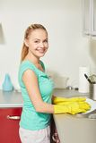 Happy woman washing dishes at home kitchen Royalty Free Stock Image
