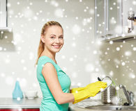 Happy woman washing dishes at home kitchen Stock Photography