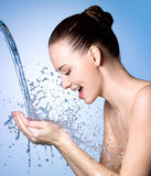 Happy woman washing face under water Stock Images