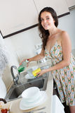 Happy woman washing plates in home Royalty Free Stock Image
