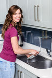 Happy woman washing plates Stock Images