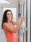 Happy woman washing windows in house Stock Image