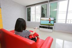 Happy woman watches television while sitting on the sofa. stock photo