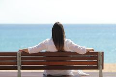 Happy woman watching the sea sitting on a bench stock photo
