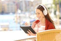 Happy woman watching streaming media content. In a tablet in a coffee shop of a coast town stock image