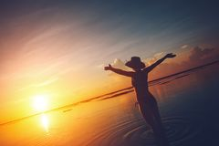 Woman watching the sun rising over the horizon at the ocean. Happy woman watching the sun rising over the horizon at the ocean Stock Photos
