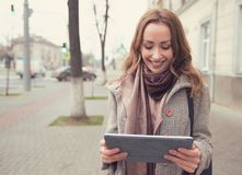 Happy woman watching tablet on street Royalty Free Stock Image
