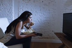 Happy woman watching television at sofa couch happy excited enjoying eating popcorn Royalty Free Stock Photo
