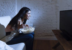 Happy woman watching television at sofa couch happy excited enjoying eating popcorn Stock Image
