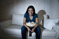 Happy woman watching television at sofa couch happy excited enjoying eating popcorn Royalty Free Stock Images