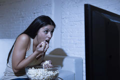Happy woman watching television at sofa couch happy excited enjoying eating popcorn Royalty Free Stock Photography