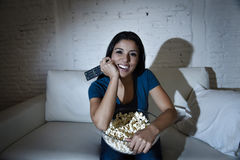 Happy woman watching television at sofa couch happy excited enjoying eating popcorn Stock Images