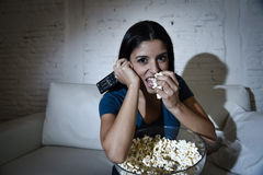 Happy woman watching television at sofa couch happy excited enjoying eating popcorn Stock Photos