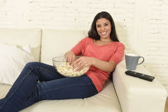 Happy woman watching television at sofa couch happy excited enjoying romantic film. Young beautiful Spanish woman in jeans home alone watching television Royalty Free Stock Photos