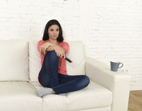 Happy woman watching television at sofa couch happy excited enjoying romantic film. Young beautiful Spanish woman in jeans home alone watching television Stock Photos