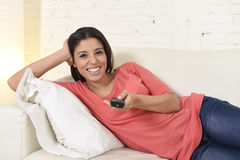 Happy woman watching television at sofa couch happy excited enjoying romantic film. Young beautiful Spanish woman in jeans home alone watching television Stock Photo