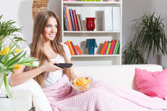 Happy woman watching TV with chips. Beautiful smiling woman watching TV with snacks Royalty Free Stock Photos
