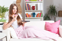 Happy woman watching TV with sweets. Happy woman watching TV with donut in hand Royalty Free Stock Photos