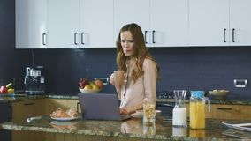 Happy woman watching video standing in kitchen. Smiling person scrolling laptop. stock video