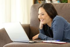 Happy woman watching videos on a laptop on a couch royalty free stock image