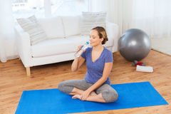 Happy woman with water bottle exercising at home Stock Photo