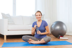 Happy woman with water bottle exercising at home Stock Image