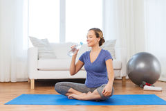 Happy woman with water bottle exercising at home Royalty Free Stock Photo