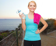 Happy woman with water bottle and towel outdoors Stock Images