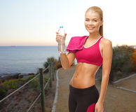 Happy woman with water bottle and towel outdoors Royalty Free Stock Image