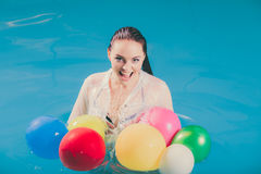 Happy woman in water having fun with balloons Stock Photos