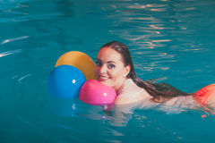 Happy woman in water having fun with balloons. Happy woman in swimming pool water having fun with balloons. Seductive young girl wearing wet white shirt relaxing Stock Photo