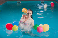 Happy woman in water having fun with balloons. Happy woman in swimming pool water having fun with balloons. Seductive young girl wearing wet white shirt relaxing Stock Photos