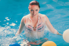 Happy woman in water having fun with balloons. Happy woman in swimming pool water having fun with balloons. Seductive young girl wearing wet white shirt relaxing Royalty Free Stock Photography