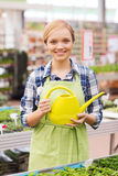 Happy woman with watering can in greenhouse Stock Photography