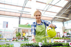 Happy woman with watering can in greenhouse Royalty Free Stock Photo