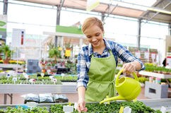 Happy woman with watering can in greenhouse Royalty Free Stock Photos