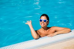 Summer vacation happiness and relax in swimming pool. Happy woman waving and enjoying summer relaxing vacation in swimming pool Royalty Free Stock Photo