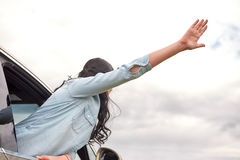 Happy woman waving hand leaning out of car window Royalty Free Stock Images