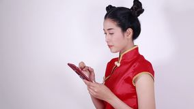 Woman wear cheongsam and using mobile phone stock footage