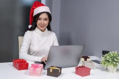 happy woman wear santa hat and christmas gift with labtop computer royalty free stock image